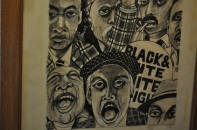 A poster showing faces in an anti-racist demo (detail).
